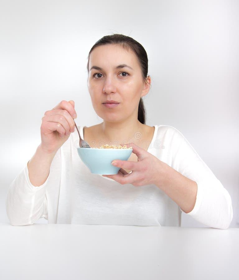 Stående av den unga kvinnan i underkläder som äter sädesslag Ung kvinna som äter sädes- muslin (flingor) fotografering för bildbyråer