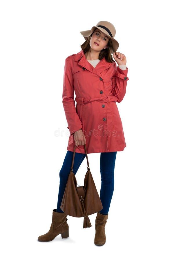 Stående av den unga kvinnan i varm klädinnehavhandväska arkivfoto
