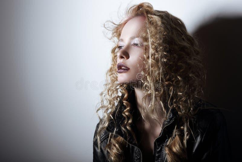 Stående av den unga kvinnan med burrigt hår arkivbilder