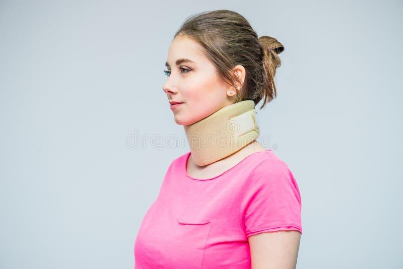 Stående av den unga kvinnan med en halsskada, en osteochondrosiskrage som ska förhindras, och en sjukgymnastik Smärta behandling  royaltyfri foto