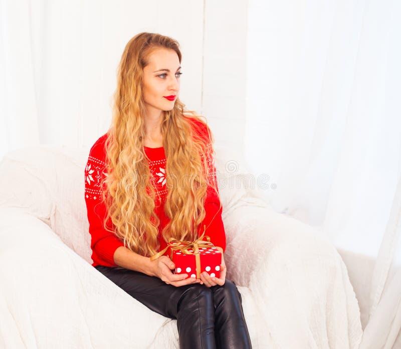Stående av den unga kvinnan med gåvaasken, medan sitta hemma arkivfoton
