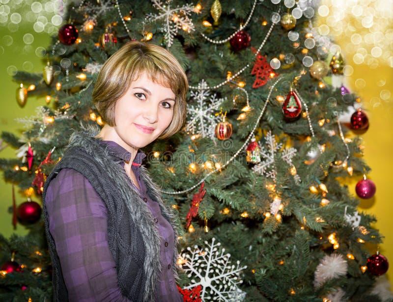 Stående av den unga kvinnan med gåvan runt om en dekorerad julgran Flicka på nytt år för ferie fotografering för bildbyråer