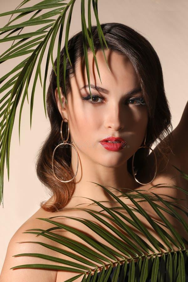 Stående av den unga kvinnan med härlig yrkesmässig makeup och palmblad på ljus bakgrund arkivfoto