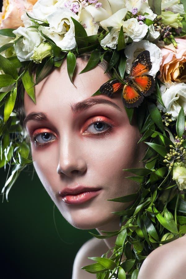 Stående av den unga kvinnan med hårgarnering av hår från sidor, blommor och fjärilar på en grön lutningbakgrund fotografering för bildbyråer