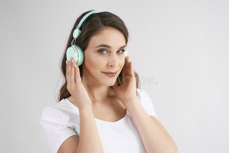 Stående av den unga kvinnan med hörlurar som lyssnar till musik royaltyfri bild