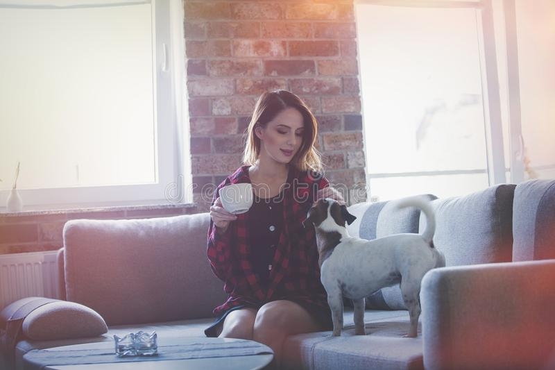 Stående av den unga kvinnan med kopp te- eller kaffesammanträde på sof royaltyfria bilder