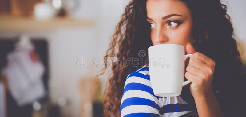 Stående av den unga kvinnan med koppen mot kökinrebakgrund royaltyfri foto