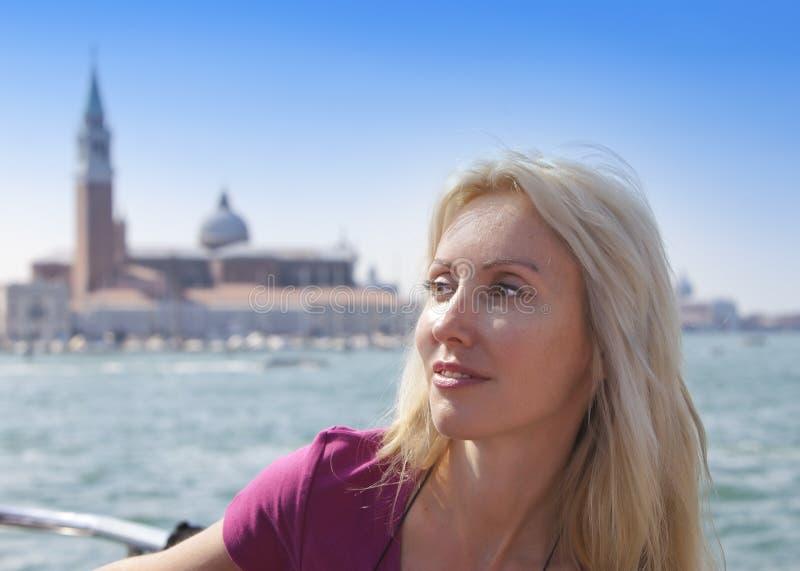 Stående av den unga kvinnan på kanalen stor och Klocka torn av basilikabackgraund italy venice royaltyfri foto