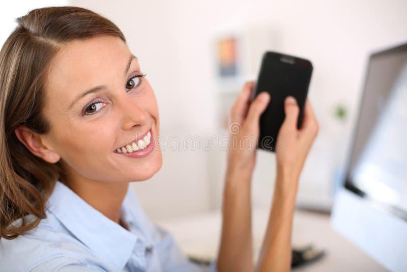 Stående av den unga kvinnan på kontoret genom att använda smartphonen royaltyfria bilder
