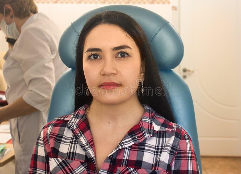 St?ende av den unga kvinnan p? stol i medicinsk klinik royaltyfria bilder