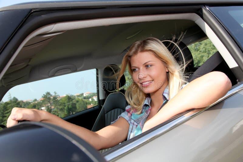Stående av den unga kvinnan på styrningshjulet royaltyfria foton