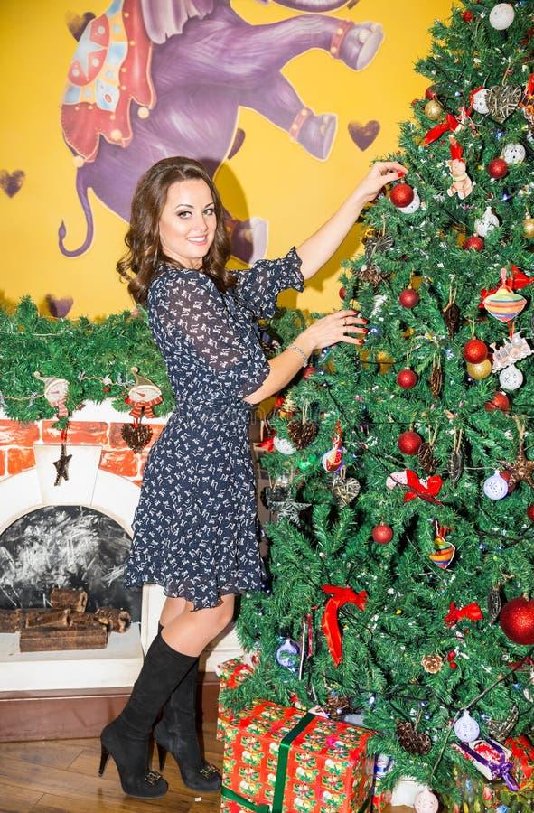 Stående av den unga kvinnan runt om en dekorerad julgran Flicka på nytt år för ferie royaltyfria foton