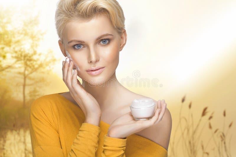 Stående av den unga kvinnan som applicerar fuktighetsbevarande hudkrämkräm royaltyfria bilder