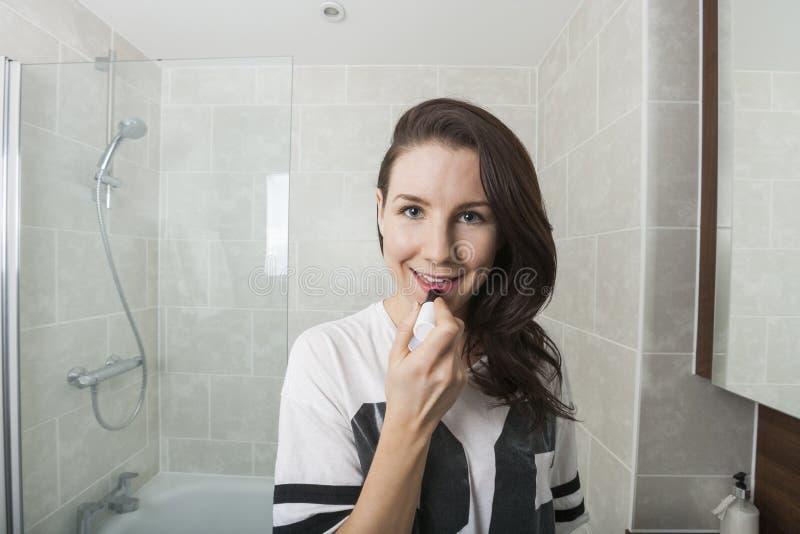 Stående av den unga kvinnan som applicerar läppstift i badrum royaltyfria bilder