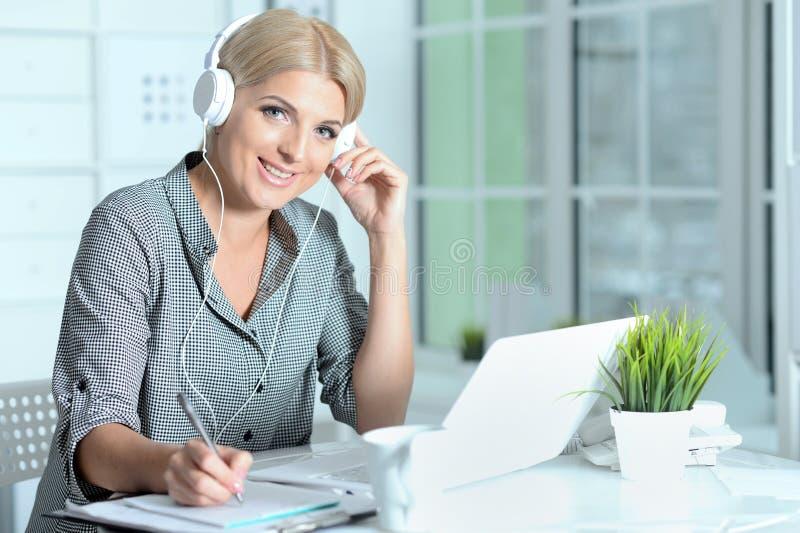 Stående av den unga kvinnan som arbetar med bärbara datorn på kontoret arkivbilder