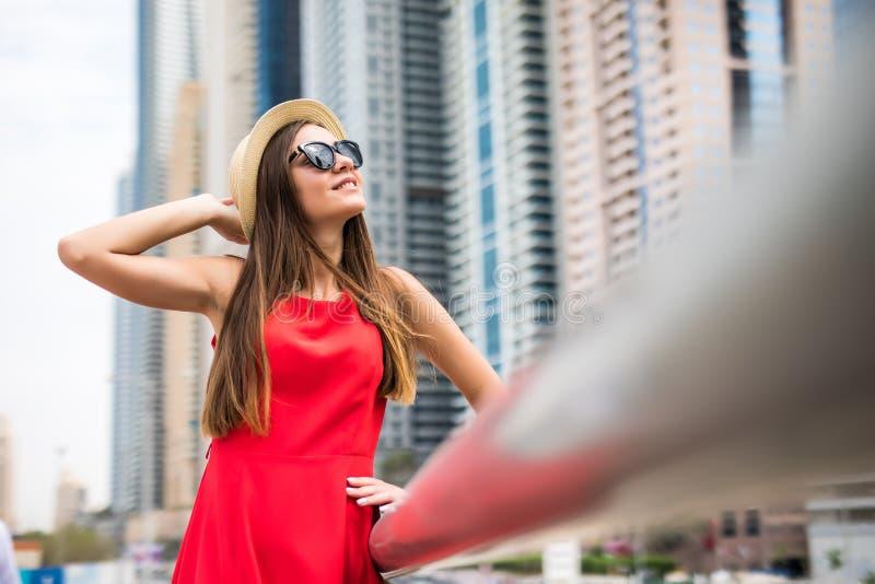 Stående av den unga kvinnan som framme bär i den röda klänningen och solglasögon, sugrörhatt av skycrapers i modern stad arkivfoto