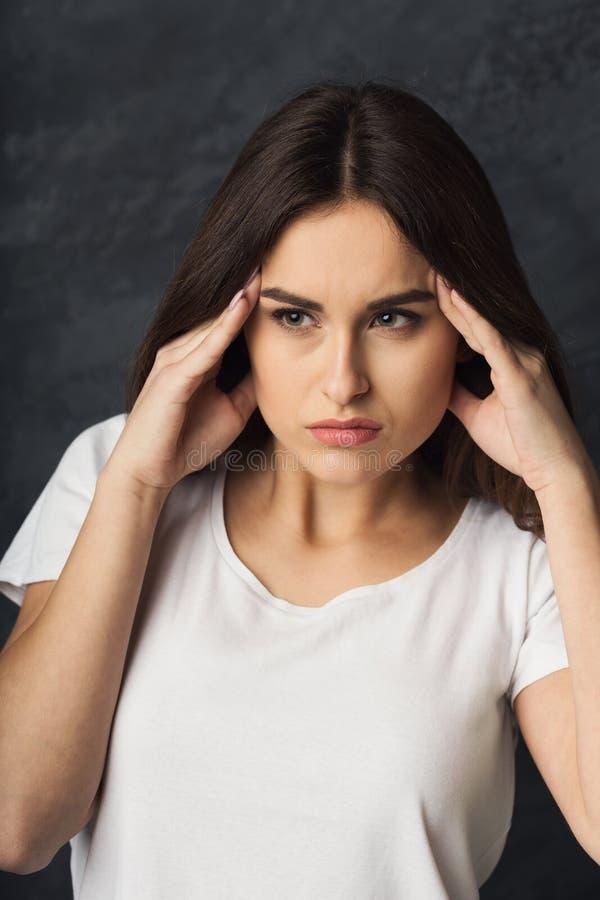 Stående av den unga kvinnan som har huvudvärk arkivbild