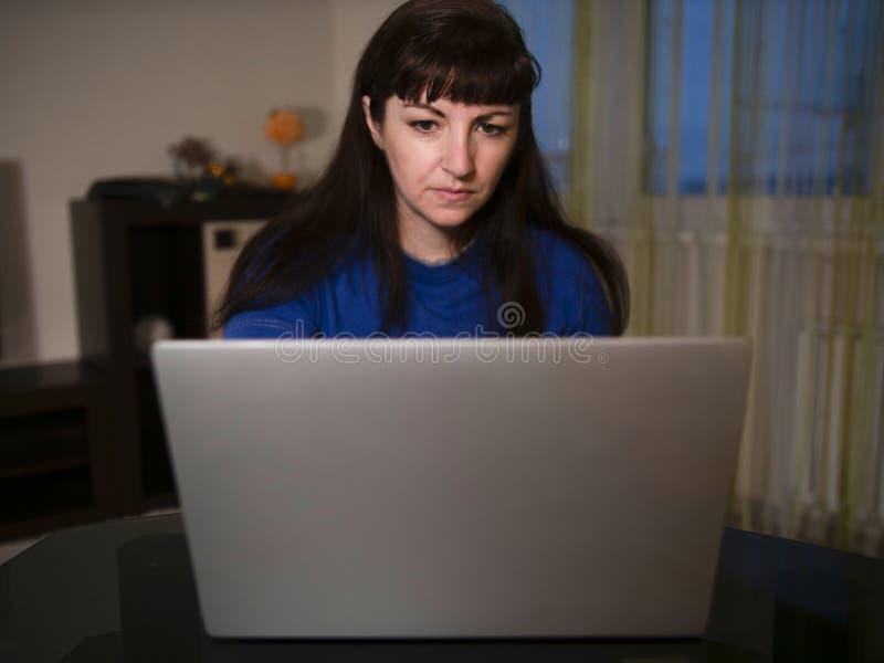 Stående av den unga kvinnan som hemma arbetar på bärbara datorn i aftonen arkivbilder