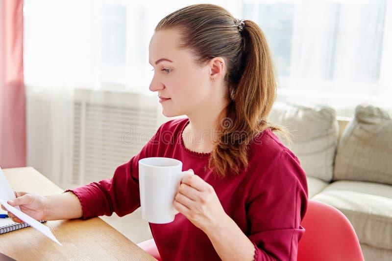 Stående av den unga kvinnan som i regeringsställning sitter på träskrivbordet med koppen kaffe och läser dokument, kopieringsutry arkivbild