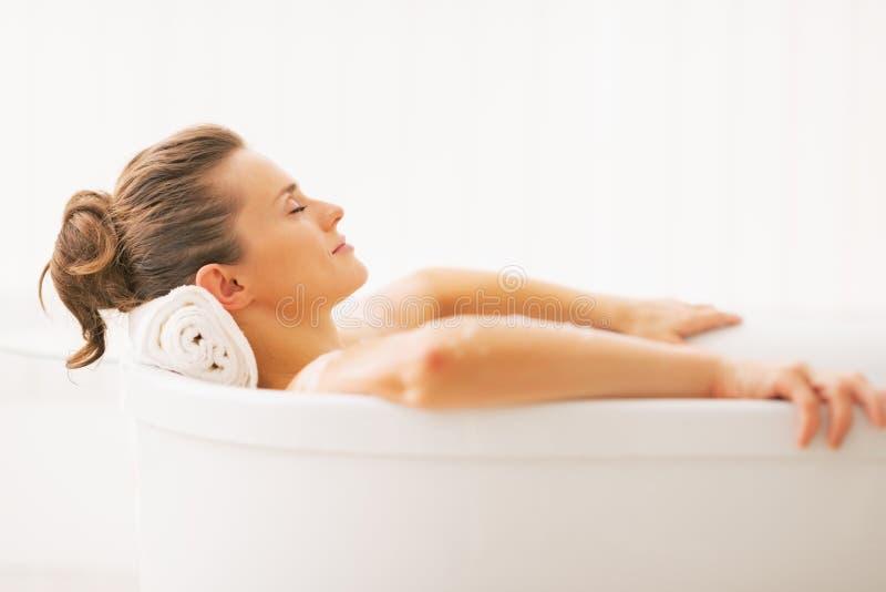 Stående av den unga kvinnan som kopplar av i badkar fotografering för bildbyråer