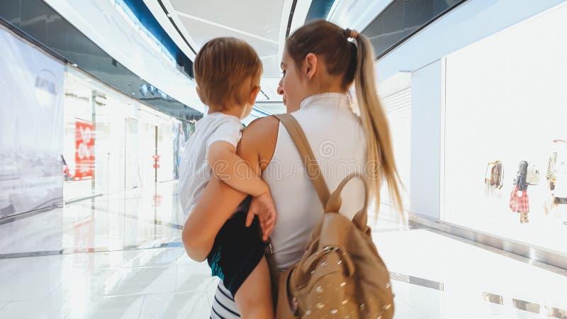 Stående av den unga kvinnan som kramar hennes lilla son och går i stor shoppinggalleria royaltyfria bilder