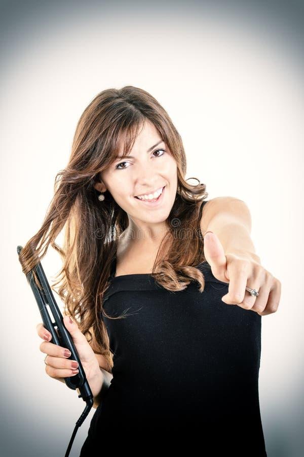 Stående av den unga kvinnan som krullar hennes hår med plant järn fotografering för bildbyråer