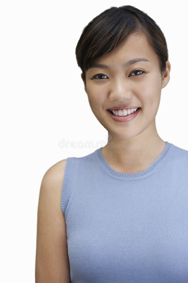 Stående av den unga kvinnan som ler mot vit bakgrund royaltyfri fotografi