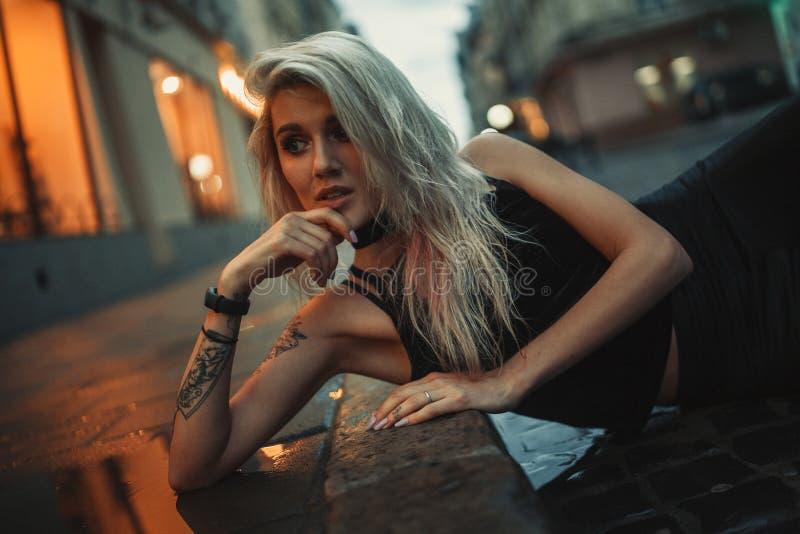 Stående av den unga kvinnan som in ligger på våt trottoar på stadsgatan royaltyfri fotografi