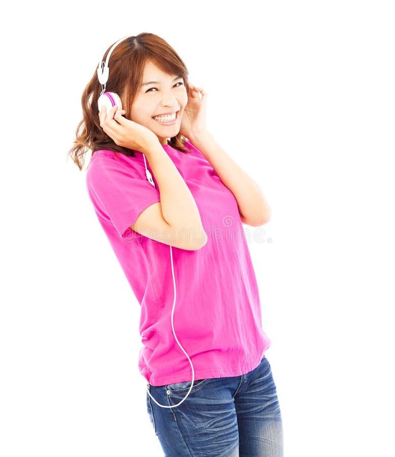 Stående av den unga kvinnan som lyssnar till musik med hörlurar arkivfoto