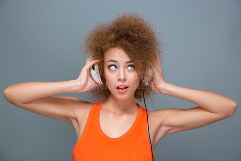 Stående av den unga kvinnan som lyssnar till musik med hörlurar arkivbild