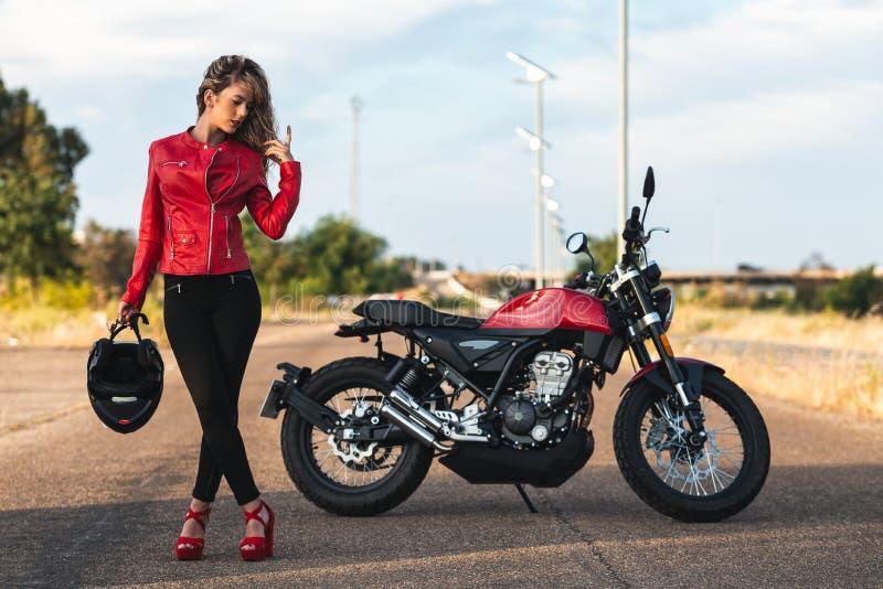 Stående av den unga kvinnan som poserar den främre klassiska mopeden royaltyfri bild