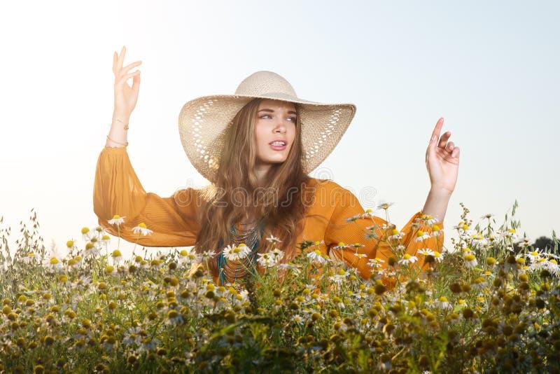Stående av den unga kvinnan som poserar i en hatt Blommande fält av tusenskönor arkivbilder