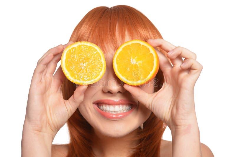 St?ende av den unga kvinnan som poserar med apelsiner p? vit bakgrund fotografering för bildbyråer