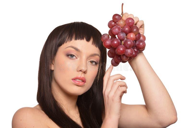 Stående av den unga kvinnan som poserar med druvor fotografering för bildbyråer