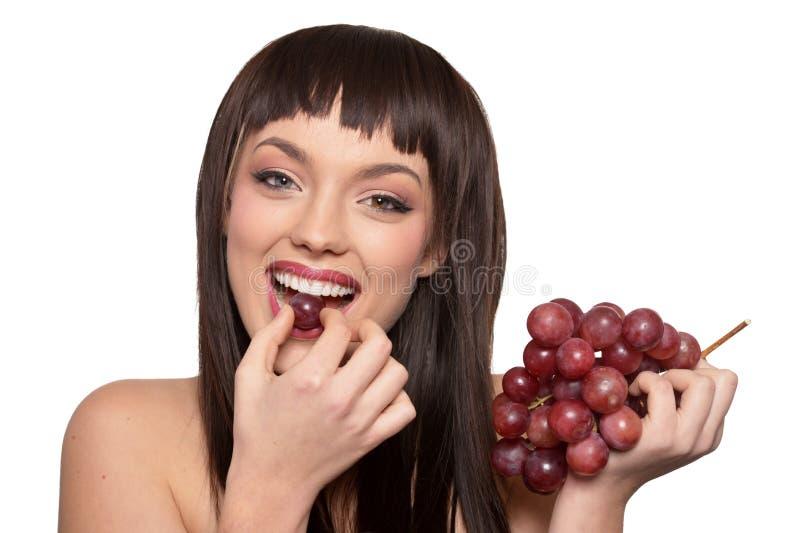 Stående av den unga kvinnan som poserar med druvor royaltyfri bild