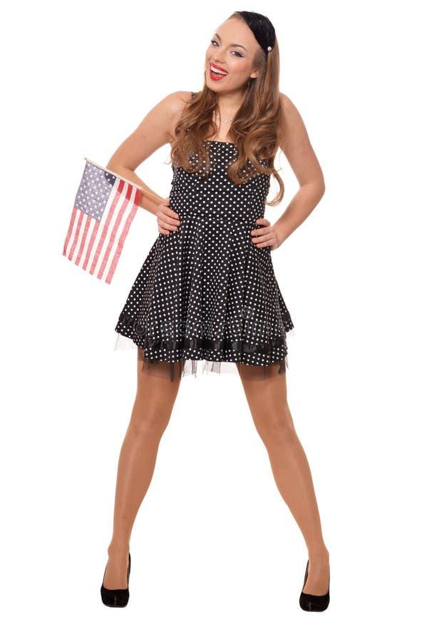St?ende av den unga kvinnan som poserar med flaggan av USA p? vit bakgrund arkivfoton