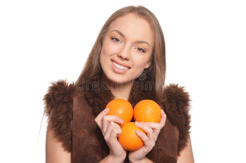 Stående av den unga kvinnan som poserar med isolerade apelsiner fotografering för bildbyråer