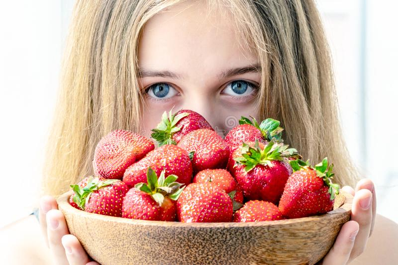 Stående av den unga kvinnan som rymmer jordgubbar i en bunke Sund lycklig le kvinna som ?ter jordgubben royaltyfria bilder
