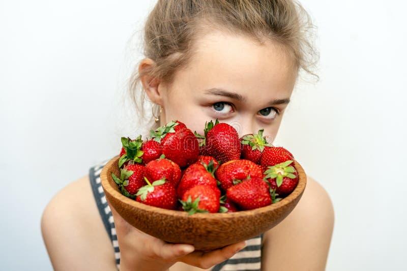 Stående av den unga kvinnan som rymmer jordgubbar i en bunke Sund lycklig le kvinna som ?ter jordgubben fotografering för bildbyråer