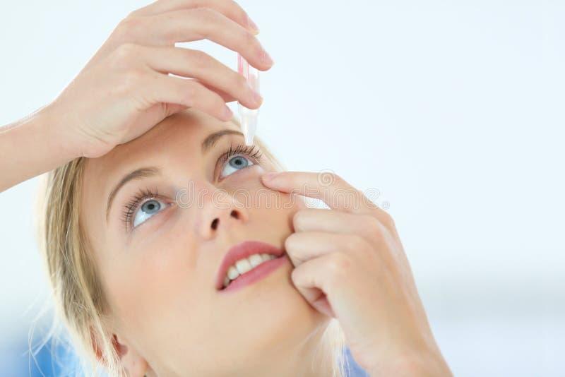 Stående av den unga kvinnan som sätter ögondroppar arkivfoton