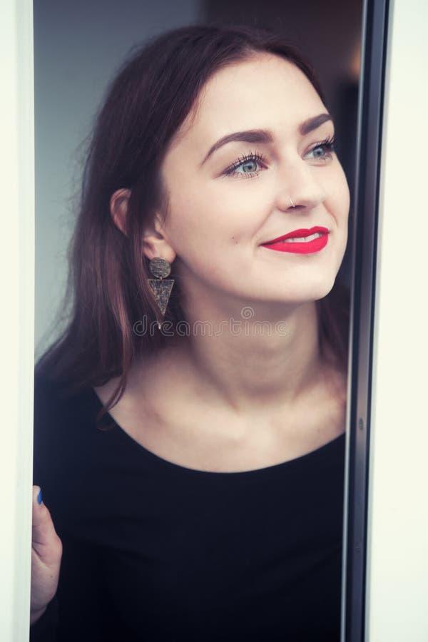 Stående av den unga kvinnan som ser ut ur fönster royaltyfria bilder