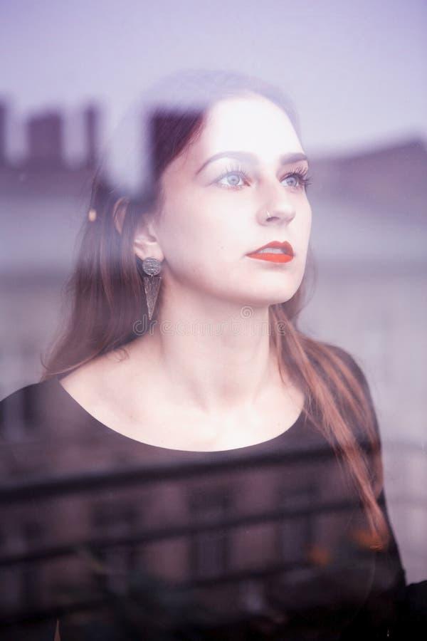 Stående av den unga kvinnan som ser ut ur fönstret arkivfoton
