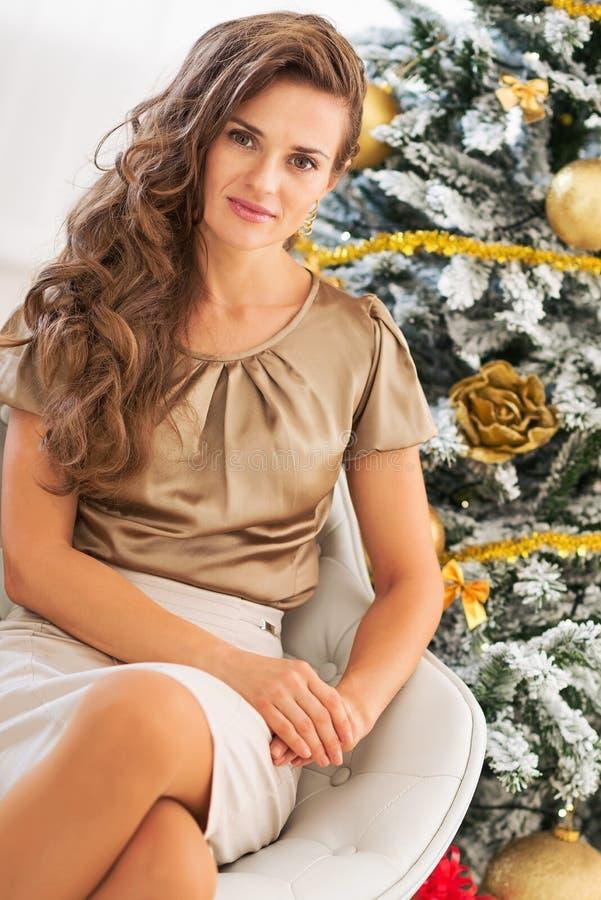Stående av den unga kvinnan som sitter nära julträd arkivfoto