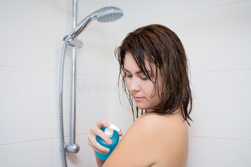 Stående av den unga kvinnan som tvättar hennes kropp i dusch arkivfoto