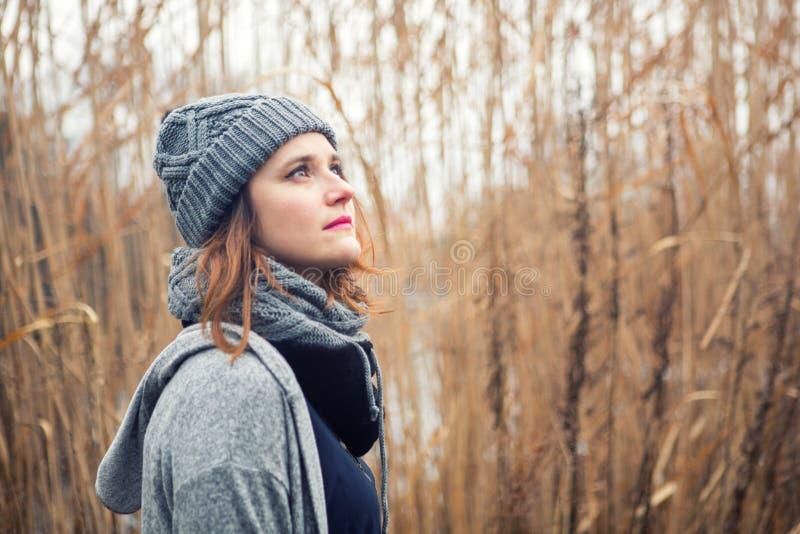 Stående av den unga kvinnan utomhus med vasser i bakgrunden arkivfoto