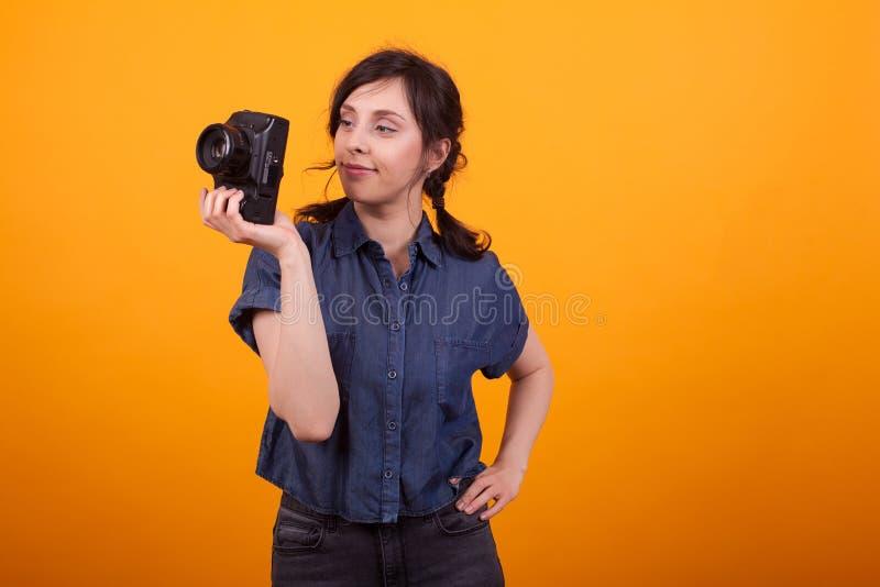 Stående av den unga kvinnliga fotografen som rymmer hennes kamera i studio över gul bakgrund royaltyfria bilder