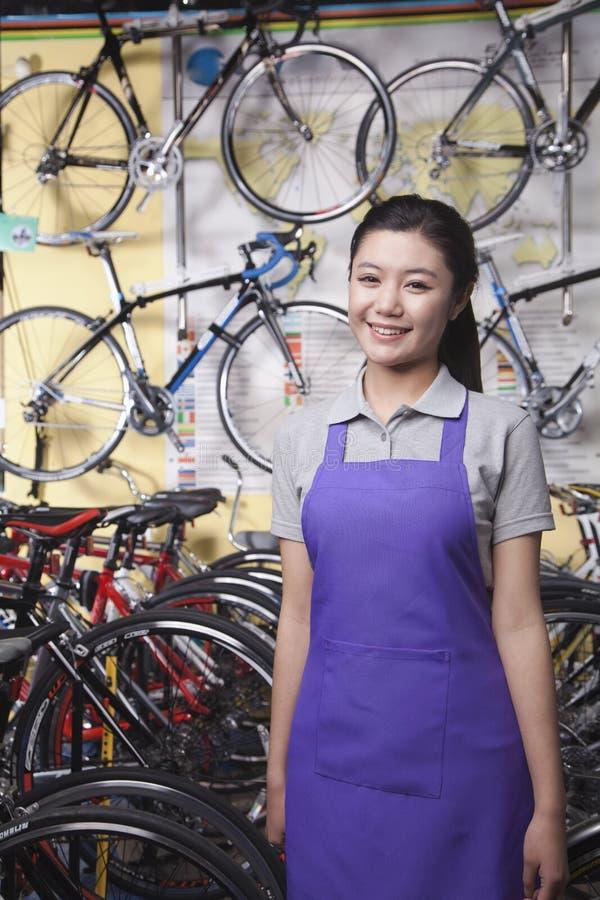 Stående av den unga kvinnliga mekanikern i cykellagret, Peking arkivbild