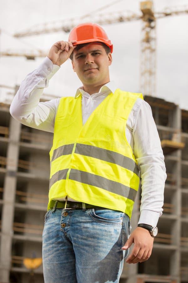 Stående av den unga le byggnadsarbetaren i hardhat på byggnadsplats royaltyfria bilder