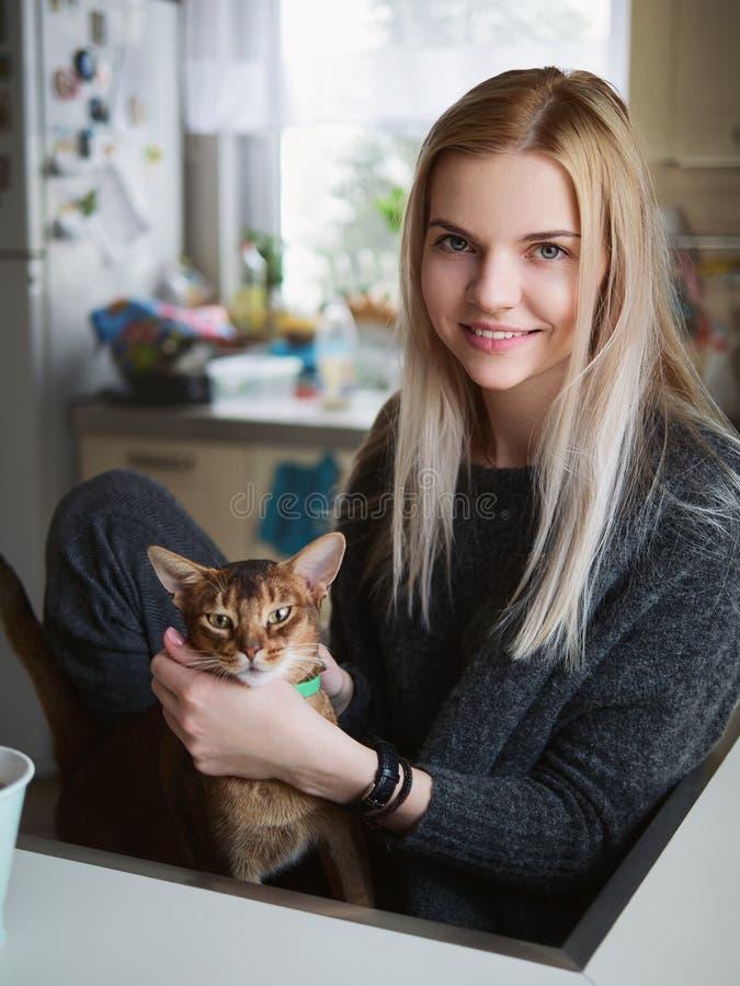 Stående av den unga le förtjusande blonda europeiska kvinnan som tycker om ögonblicket som daltar den abyssinian katten som poser royaltyfria bilder