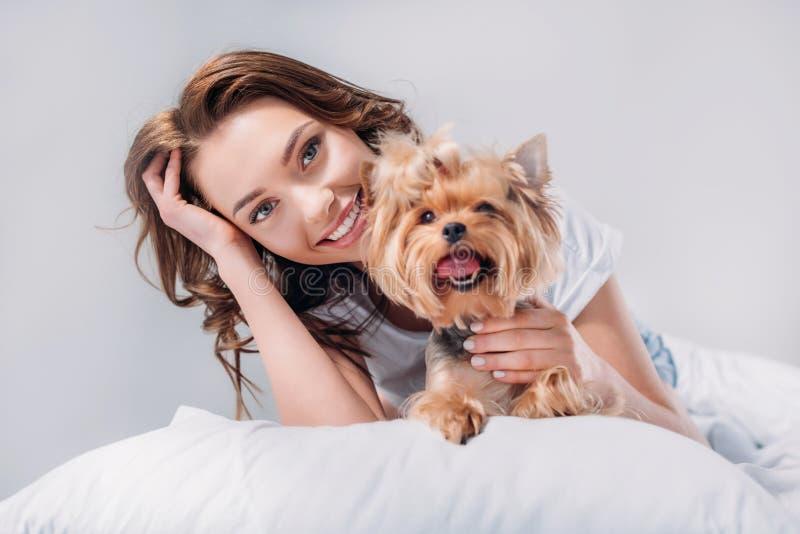 stående av den unga le kvinnan med den yorkshire terriern som vilar på säng arkivbilder